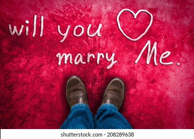 "love concept with Brown leather shoes and hand drawn text "" Will You marry me "". red pink grunge background"