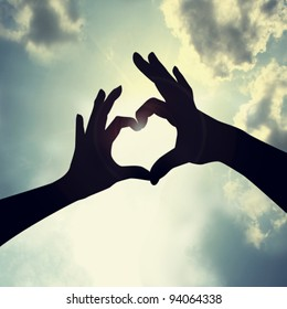 love shape hand silhouette in sky