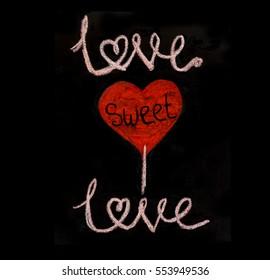 """""""Love sweet love"""" is a message handwritten with chalk on a blackboard."""