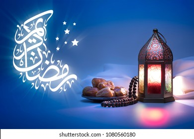 Low light photo of Lantern, Dates fruit and rosary beads with Arabic Calligraphy : Ramadan Mubarak for greeting cards