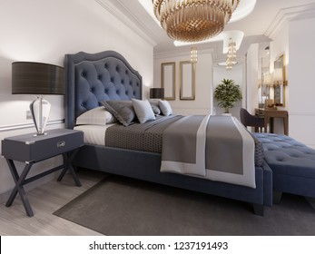 A luxurious bedroom in a classic style with gold elements and a blue bed cloth and a wooden dresser and dressing table. 3d rendering.
