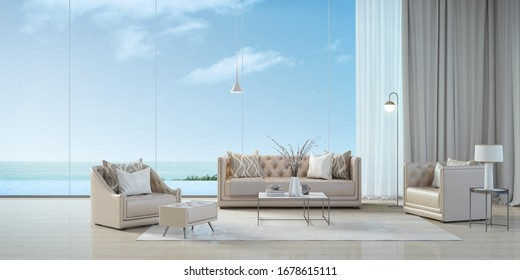 Luxury beach house.Sofa,armchair,stool,side table,lamps,curtains in living room with infinity edge swimming pool and sea view outside.Vacation home or holiday villa.3d rendering