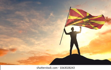 Macedonia flag being waved by a man celebrating success at the top of a mountain. 3D Rendering