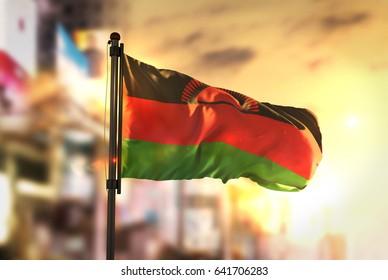 Malawi Flag Against City Blurred Background At Sunrise Backlight 3D Rendering