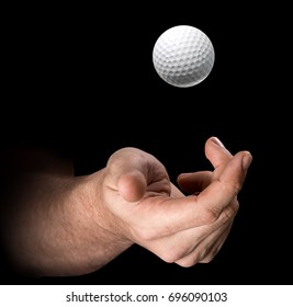 A male hand tossing a golf ball up in the air on an isolated dark background - 3D render