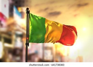 Mali Flag Against City Blurred Background At Sunrise Backlight 3D Rendering