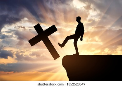 Man atheist pushes the symbol of christian cross into the cliff on sunset background. Concept of atheism