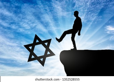 Man atheist pushes the symbol of Judaism into the abyss. Concept of atheism