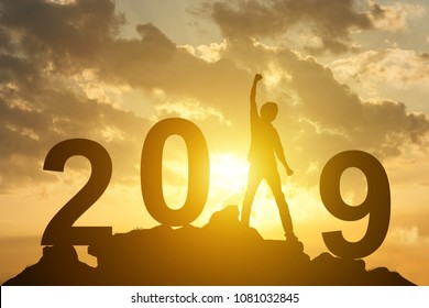 Man hand up on the peak of mountain and sunlight  with text 2019 happy new year calendar holiday concept