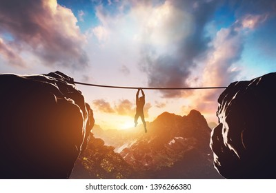 Man hanging on rope between two high mountains at sunset. Concept of taking a risk, danger, challenge. 3D illustration