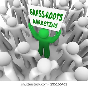 A man holding a Grass Roots Marketing sign in a crowd to illustrate local advertising and spreading word of mouth to promote your product or service