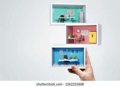 A man Holding up a stack of miniature business office rooms. Business workplace 3D concept illustration.