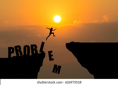 Man jumping over Problem text over cliff on sunset background,Business concept idea