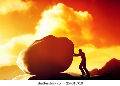 Man pushing a giant, heavy stone, rock over the mountain. Conceptual, struggle, difficult task.