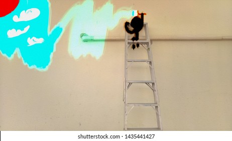 man sitting on the ladder painting the white wall with light blue color