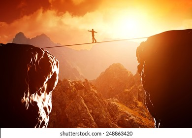Man walking and balancing on rope over precipice in mountains at sunset. Concept of business, risk taking, challenge, concentration.