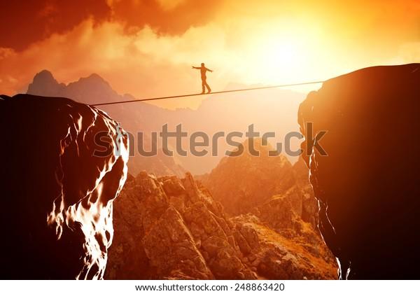 Человек ходит и балансирует на веревке над пропастью в горах на закате. Понятие бизнеса, риск, вызов, концентрация.