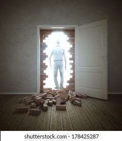 Man walking through an opening in a brick wall blocking the doorway