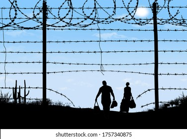 A man and woman are seen in silhouette after breaching a border fence on the southern border of the USA. They have gone through a broken barbed wire fence.