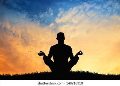 man in yoga pose at sunset