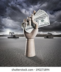 Manikin hand holding money in dry lake bed with storm clouds and drilling rigs in background