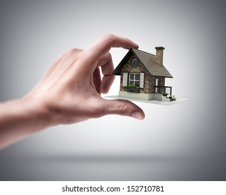 Man's hand holding house