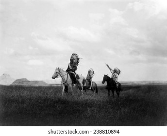 The March of the Sioux, three Sioux Indians on horseback on plains with rock formations in background, photograph by Edward S. Curtis, 1905