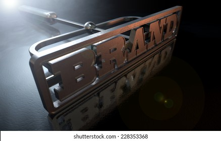 A metal cattle brand with the word brand as the marking area on an isolated dark backlit surface and background