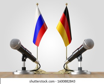 Microphones and Russian and German flags pair on a desk over isolated background.3d illustration