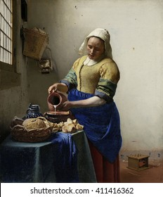The Milkmaid, by Johannes Vermeer, 1660, Dutch painting, oil on canvas. Illuminated by light from a window, a young woman pours milk into a cooking pot next to a wicker basket of bread. In lower righ
