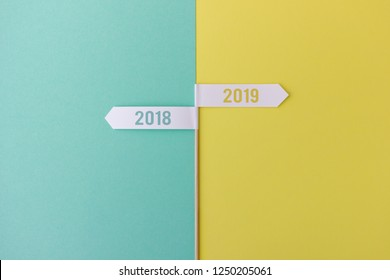 Minimalist composition of wood stick with flags showing towards the years 2018 and 2019 on colorful background