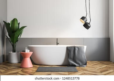 Minimalistic bathroom interior with white and gray walls, wooden floor, white bathtub with gray towel on it and pink chair. Potted plant. 3d rendering