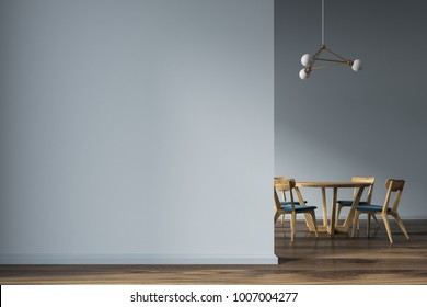Minimalistic gray dining room interior with a wooden floor, and a round wooden table with wooden and blue chairs. A blank wall fragment. 3d rendering mock up