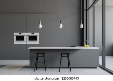 Minimalistic gray kitchen interior with gray walls, concrete floor, loft windows, gray cupboard with built in ovens and gray bar with stools next to countertops with sink. 3d rendering