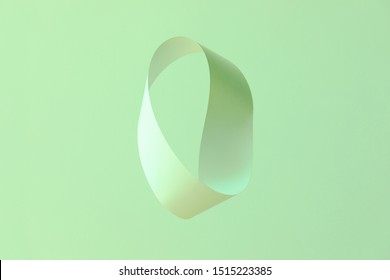 Mobius strip made from paper soaring in the air on mint background. Trendy surreal airy image. Abstract color concept composition with copy space.