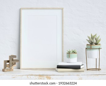 Mock up poster frame on white plaster wall with echeveria plants in pots, books and geometric object on old wooden table; portrait orientation; stylish frame mock up; 3D rendering, 3D illustration