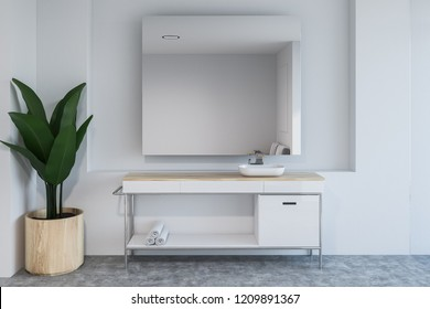 Modern bathroom interior with white walls, concrete floor, sink standing on white countertop and large mirror. 3d rendering