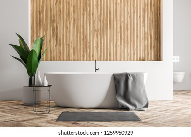 Modern bathroom interior with white and wooden walls, wooden floor, white bathtub with a towel on it and a carpet near it and a toilet. 3d rendering