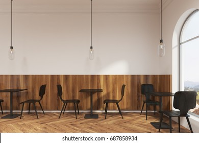 Modern black chairs are standing near square wooden tables in a coffee shop or a restaurant with a wooden floor and white walls. 3d rendering