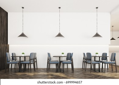 Modern cafe interior with white and wooden walls, a wooden floor, square tables surrounded by gray chairs and many ceiling lamps. 3d rendering