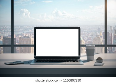 Modern designer office workplace with empty white laptop screen, coffee cup, some supplies and panoramic city view with daylight. Mock up, 3D Rendering