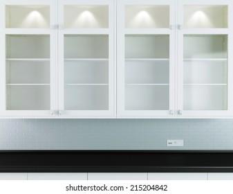 Modern kitchen design, white furniture with black worktop.