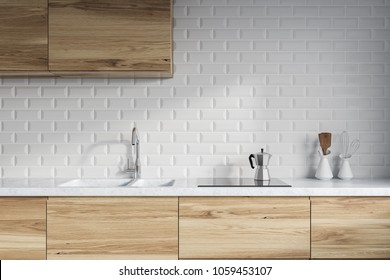 Modern kitchen interior with white brick walls, wooden countertops with a built in sink and a cooker. 3d rendering mock up