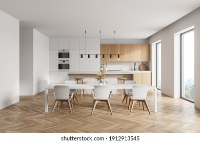 Modern kitchen interior with white walls, a wooden parquet floor and white countertops. A long table with chairs near it. 3d rendering