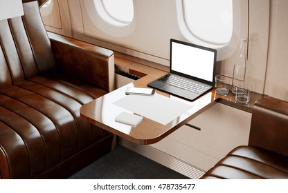 Modern Laptop Blank Screen Inside Interior Wood Table Luxury Private Airplane Jet.Empty Leather Chair Generic Design Notebook.Clear White Display Ready Business Information.Crops Mockup.3d rendering