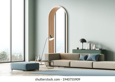 Modern living room interior with arch, mint color on wall and panoramic windows, hills view. Beige sofa with blue cushions, coffee table, light green chest of drawers. Parquet floor. 3D rendering