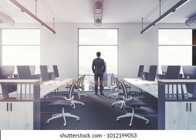 Modern office interior with white walls, large windows, white desks and black office chairs. An African American businessman 3d rendering mock up toned image