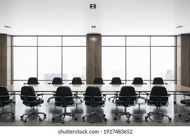 Modern spacious meeting room with big window, wooden table in the center and black chairs around. 3D rendering