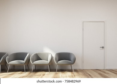 Modern waiting area with white walls, a wooden floor and a row of soft gray armchairs. 3d rendering mock up