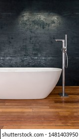 Modern white boat-shaped bathtub with tall chrome faucet on wooden floorboards in front to a textured grey wall. 3d rendering
